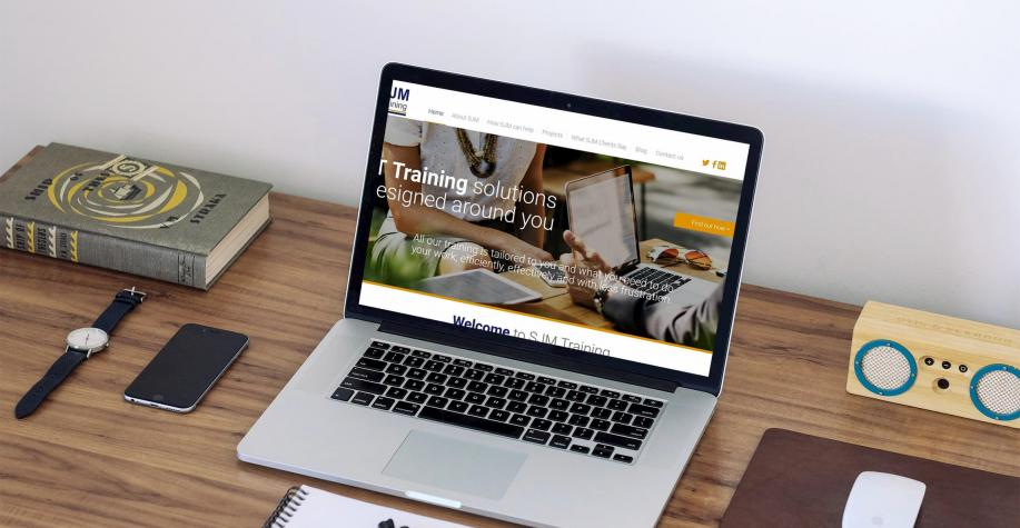 SJM Training website displayed on a macbook