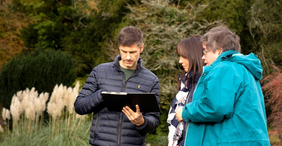 A man showing two women how to use an ipad